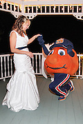 Bride standing in a lighted gazebo while Otto the Syracuse University mascot kneels to propose to her at Gilfillan's West Hill, Camillus, NY