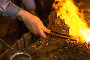 A blacksmith forges red hot steel over the flame in an metal work shop in Charleston, SC