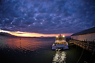 Boat anchored in Port Douglas harbor at sunset.