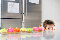 Young boy peaking over counter at row of cupcakes in kitchen