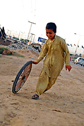 59577853 .An Afghan refugee boy plays with a tire at a slum on the outskirts of Islamabad, capital of Pakistan on April 27, 2013.  The UN refugee agency (UNHCR) said on Wednesday that over 83,000 Afghan refugees were repatriated from Pakistan in 2012, on April 27, 2013, 29, April. Photo by: i-Images.UK ONLY