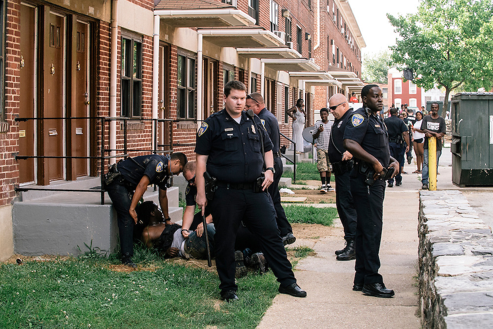 Police respond to a call for an armed person at the Gilmor Apartments in the western district of Baltimore on July 28, 2015. Arrests have gone down by nearly 50 percent while homicides and non-fatal shootings have soared in the city since the death of Freddie Gray.