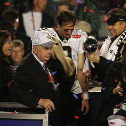 2010 February 07: New Orleans Saints head coach Sean Payton and quarterback Drew Brees (9) celebrates with owner Tom Benson and Rita Benson LeBlanc on stage following a 31-17 win by the New Orleans Saints over the Indianapolis Colts in Super Bowl XLIV at Sun Life Stadium in Miami Gardens, Florida.