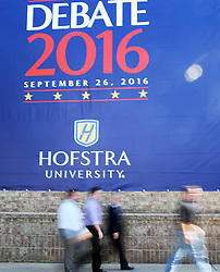 Sept. 26, 2016 - New York, New York, U.S. - People walk by the debate poster on the wall outside the media center for the first U.S. presidential debate at Hofstra University. The first of three presidential debates between the Democratic and Republican nominees, Hillary Clinton and Donald Trump, will be held Monday at Hofstra University in New York.  (Credit Image: © Qin Lang/Xinhua via ZUMA Wire)