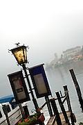 Lantern and the island monastery of Isola San Giulio from the harbor of Orta San Giulio, Piedmont, Italy.