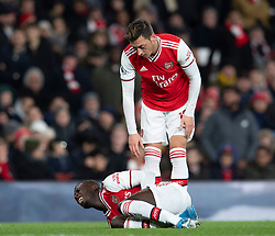LONDON, ENGLAND - Thursday, December 5, 2019: Arsenal's Nicolas Pépé lies injured as Mesut Özil stands over him during the FA Premier League match between Arsenal FC and Brighton & Hove Albion FC at the Emirates Stadium. (Pic by Vegard Grott/Propaganda)