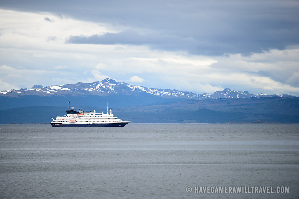 A cruise ship anchored in the Beagle Channel just off Ushuaia, Argentina, with snow-covered mountains in the background. The snow-capped mountains in the distance are across the Beagle Channel in Chile.