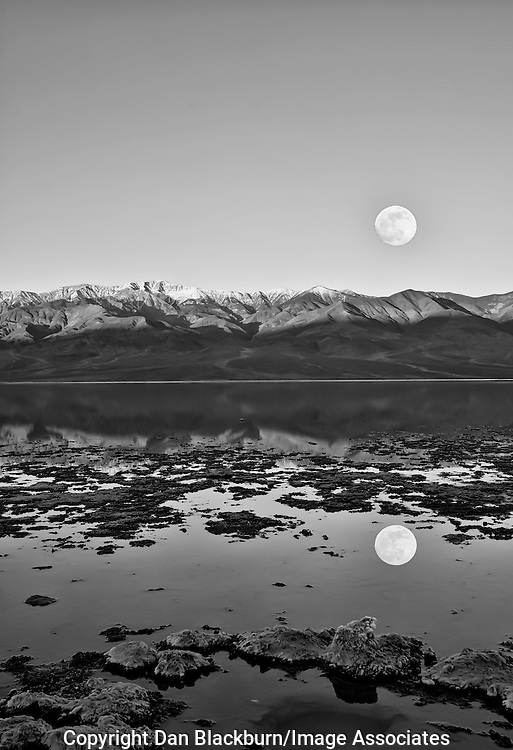 The full moon sets over Telescope Peak & the Panamint Mountains & is reflected in Badwater, the lowest point in Death Valley, California