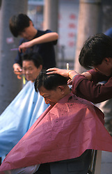 CHINA SHANGHAI MAY99 - Two barbers cut the hair of two Chinese men at the open-air store in the streets of downtown Shanghai. jre/Photo by Jiri Rezac