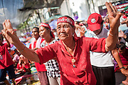 """09 MAY 2010 - BANGKOK, THAILAND: A Red Shirt woman cheers for Red Shirt speakers at the Red Shirt rally in Bangkok Sunday. The Red Shirt leaders said Sunday they still conditionally supported the Prime Minister's """"Road Map to Reconciliation"""" but that their opponents the Yellow Shirts needed to sign on to make the five point """"Road Map"""" viable. About 5,000 people mostly from northeast Thailand, joined the Red Shirts in Ratchaprasong over the weekend. Members of the United Front of Democracy Against Dictatorship (UDD), also known as the """"Red Shirts"""" and their supporters have occupied Ratchaprasong intersection, the site of Bangkok's fanciest shopping malls and several 5 star hotels, since April 4. The Red Shirts are demanding the resignation of current Thai Prime Minister Abhisit Vejjajiva and his government. The protest is a continuation of protests the Red Shirts have been holding across Thailand. They support former Prime Minister Thaksin Shinawatra, who was deposed in a coup in 2006 and went into exile rather than go to prison after being convicted on corruption charges. Thaksin is still enormously popular in rural Thailand.   PHOTO BY JACK KURTZ"""