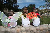Three girls (7-12) wearing costumes sitting in park