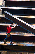 Overview of a construction worker guiding a steel beam on a commercial building work site.