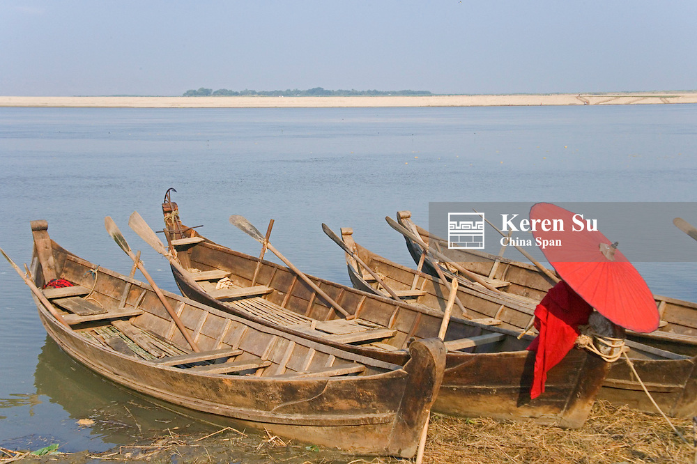 Monk with boats moored along the Ayeyarwadi River, Myanmar