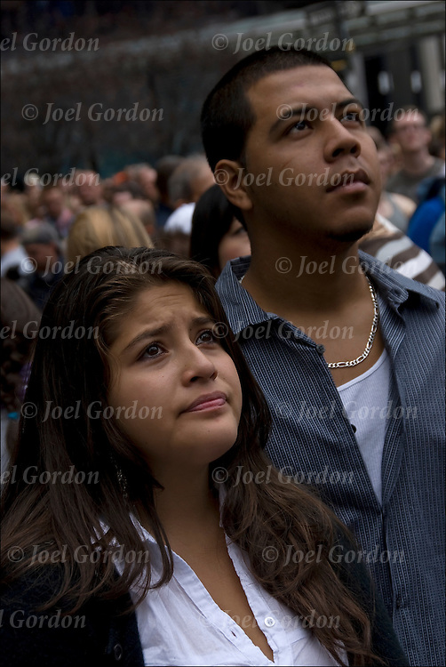 Hispanic couple looking up in silence and remembrance at large video screen as names of the 9-11-11 are read.