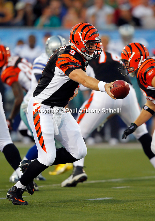 Cincinnati Bengals quarterback Carson Palmer (9) hands off the ball on a running play during the NFL Pro Football Hall of Fame preseason football game between the Dallas Cowboys and the Cincinnati Bengals on Sunday, August 8, 2010 in Canton, Ohio. The Cowboys won the game 16-7. (©Paul Anthony Spinelli)