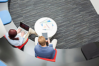 High angle view of business people using technologies in office