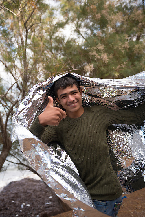A young migrant from Afghanistan gives a thumbs-up gesture while walking on the coast of the Greek island of Lesbos to a registration center. He was given a foil blanket earlier in the morning after having arrived by boat from Turkey.