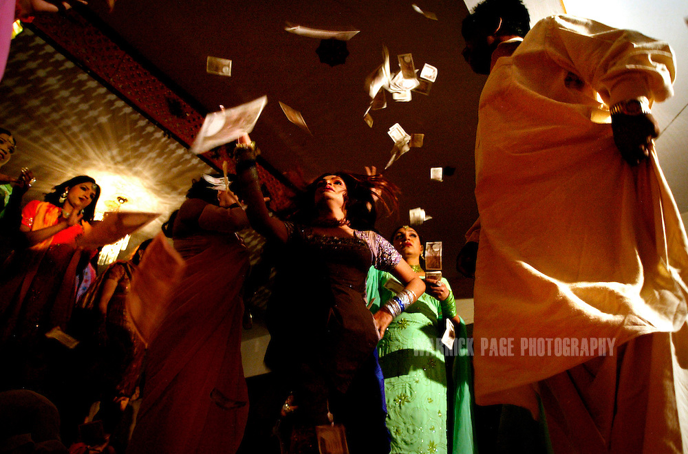 "Hijras (eunuchs) throw money over a dancer during an underground party, June 16, 2005, Rawalpindi, Pakistan. The suspected hideout of Osama Bin Laden, Al Qaeda leaders and countless Islamic militants, Pakistan is also home to one of the subcontinents largest communities of transsexuals, eunuchs and transvestites, or as they are more commonly known - Hijras. Caught between modernity and fundamentalism at the frontline in the war against terror, the Islamic Republic is a country at war with its own identity, yet its Kushras (Urdu for eunuch) stand out as a tight-nit community of devout Muslims. As Pakistan's most marginalised community, they live in fear ""24 hours a day"", according to the group She-male Rights of Pakistan. Hijras are considered by many as unclean, amoral, drug users, and who also have the ability to place curses. Many people fear their curse so gravely, they will give generously when a Kushra comes to beg in their neighbourhood and ask them for Allah's blessing.. (Photo by Warrick Page)"