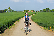 A tourist is cycling on the road towards Stamford Bridge, Yorkshire, England, United Kingdom.