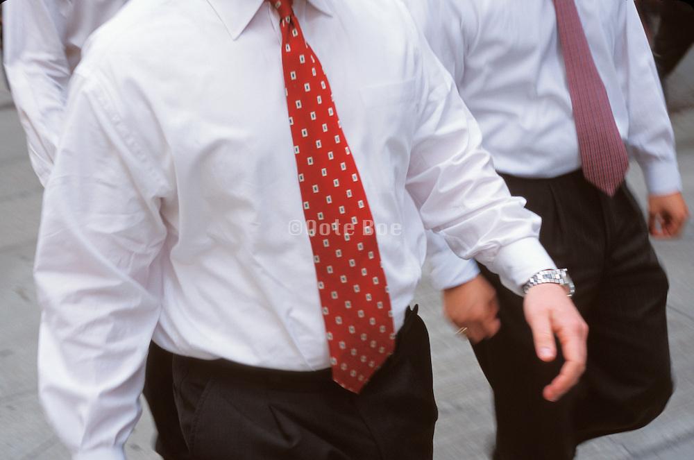 Three business men in white shirts walking