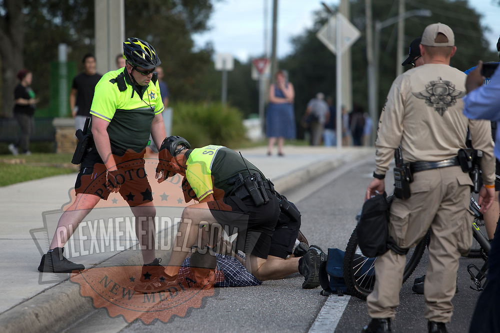 Police take down a man who rode his bike through the staging site prior to a Richard Spencer speech at the Phillips Center for the Performing Arts on the University of Florida campus in Gainesville, Florida on Thursday, October 18, 2017. (Alex Menendez)