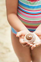 Girl (7-9 years) holding sea shell in clasped hands mid section elevated view