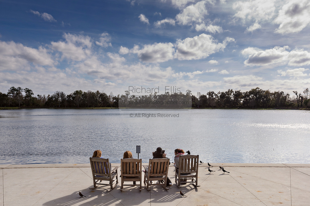 People sit relaxing along Spring Lake in the Disney created master planned community of Celebration, Florida.