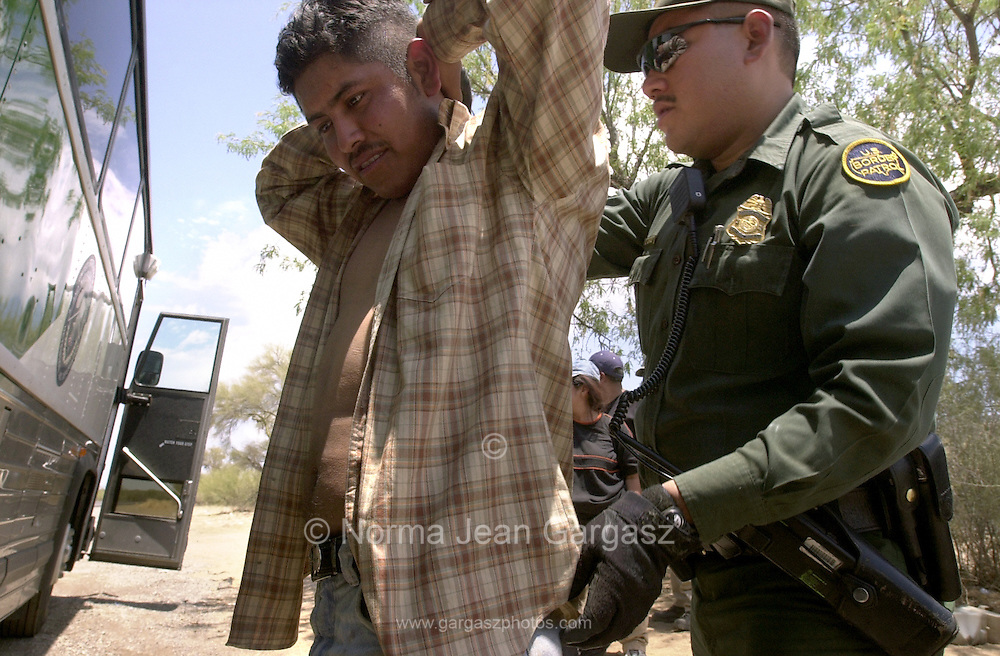 A U. S. Border Patrol agent, (right), prepares to deport an illegal immigrants from Mexico near Sells, Arizona on the Tohono O'odham Nation.  This area has the highest death rate of illegal border crossers in the nation.