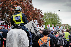 Mounted Police form a cordon as anti-fascists gather to protest against a march held by the English Defence League. May 2015, Walthamstow London