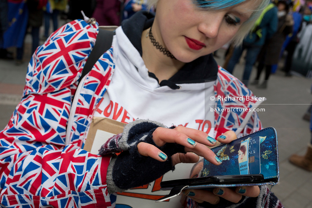 On the day that Prime Minister Theresa May's Meaningful Brexit vote is taken in the UK Parliament, a protesting Remainer uses her phone opposite the House of Commons, on 15th January 2019, in Westminster, London, England.