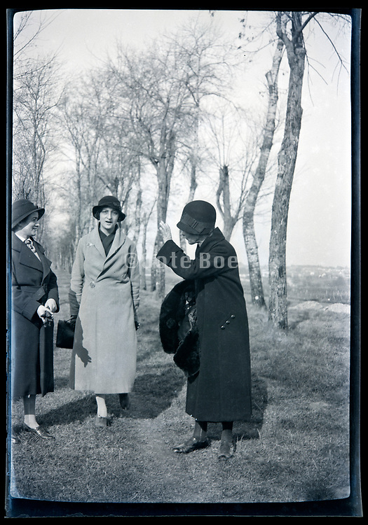 women standing and talking in a rural landscape with a trees lined path France circa 1920s