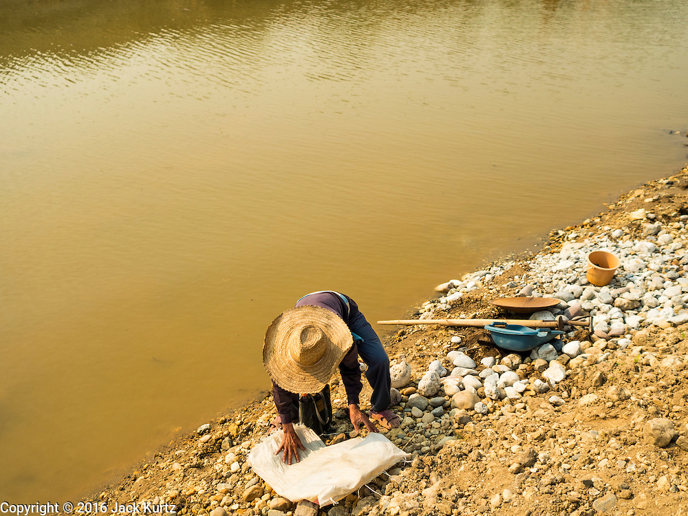 """01 APRIL 2016 - WANG NUEA, LAMPANG, THAILAND:  A man gets ready to pan for gold in the Mae Wang. Villagers in the Wang Nuea district of Lampang province found gold in the Mae Wang (Wang River) in 2011 after excavation crews dug out sand for a construction project. A subsequent Thai government survey of the river showed """"a fair amount of gold ore,"""" but not enough gold to justify commercial mining. Now every year when the river level drops farmers from the district come to the river to pan for gold. Some have been able to add to their family income by 2,000 to 3,000 Baht (about $65 to $100 US) every month. The gold miners work the river bed starting in mid-February and finish up by mid-May depending on the weather. They stop panning when the river level rises from the rains. This year the Thai government is predicting a serious drought which may allow miners to work longer into the summer. The 2016 drought has lowered the water level so much that the river is dry in most places and people can only pan for gold in a very short stretch of the river.     PHOTO BY JACK KURTZ"""