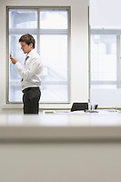 Businessman standing by desk in office sending text message