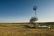 Windmill pumping water in northeast New Mexico.  Many of these windmills have been replaced by electric pumps, but in some remote areas without electricity they still use the old fashioned windmills to pump water for livestock.