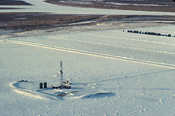 Stock photo of an workover rig in a snowy field in Wyoming.