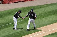 CHICAGO - JULY 09:  A.J. Pierzynski #12 shakes hands with third base coach Jeff Cox #8 of the Chicago White Sox after Pierzynski hit a home run against the Cleveland Indians on July 9, 2009 at U.S. Cellular Field in Chicago, Illinois.  The Indians defeated the White Sox 10-8.  (Photo by Ron Vesely)