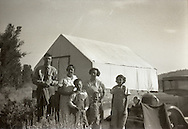 A family poses for a black and white photo during the 1930s or 1940s in a rural setting next to a Ford Model A car and a tent style structure.