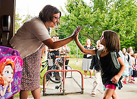 Principal Tara Beauchemin gives high fives to incoming kindergarteners at Elm Street School on Tuesday morning.  (Karen Bobotas/for the Laconia Daily Sun)