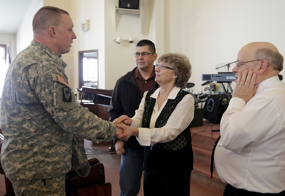 Army National Guard Lt. Colonel James Bridgman (L) greets Cathy Hagen (2nd R) and husband, Reverend Les Hagen (R), following service at the Glad Tidings Assembly of God church in Darrington, Washington March 30, 2014. Local churches offered prayers on Sunday for the victims of last week's devastating mudslide in Washington state and words of solace for grieving families and friends, many of whom are still waiting for news of missing loved ones. The presumed body count stood at 28 from the March 22 catastrophe northeast of Seattle, with the official tally of those killed at 18, based on bodies extricated and identified by medical examiners.  REUTERS/Jason Redmond (UNITED STATES)