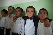 Boys in school uniform pose for a photograph in Mombekova School (in Osh, Kyrgyzstan) during the ceremony to mark the 'first bell', or first day of school, on September 1, 2010.