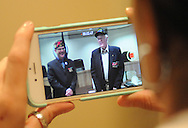Clarice Latham makes a video as World War II Veteran, Robert K. Patterson (right) is presented with the Bronze Star Medal by State Director, Bob DeSousa (left), COL USAR JA at the Horsham Township Building Friday August 7, 2015 in Horsham, Pennsylvania. (Photo by William Thomas Cain)