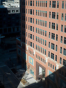 """29 MARCH 2020 - DES MOINES, IOWA: A person stands in the sun in front of an office tower on an empty street in downtown Des Moines. On Sunday morning, 29 March, Iowa reported 336 confirmed cases of the Novel Coronavirus (SARS-CoV-2) and COVID-19. There have been four deaths attributed to COVID-19 in Iowa. Restaurants, bars, movie theaters, places that draw crowds are closed until 07 April. The Governor has not ordered """"shelter in place""""  but several Mayors, including the Mayor of Des Moines, have asked residents to stay in their homes for all but the essential needs. People are being encouraged to practice """"social distancing"""" and many businesses are requiring or encouraging employees to telecommute.       PHOTO BY JACK KURTZ"""