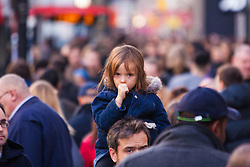 "London, December 20th 2014. Tens of thousands of shoppers descend on central London to scoop up pre-Christmas bargains as retailers offer discount incentives on ""Panic Saturday"". PICTURED: A little girl gets an elevated view of the thousands of Christmas shoppers as she rides on a man's shoulders on Oxford Street."