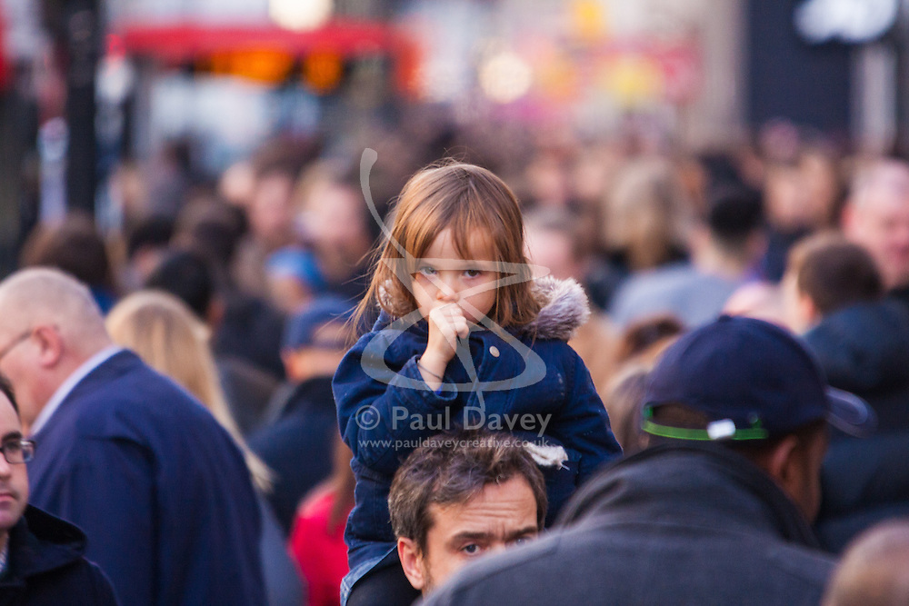 """London, December 20th 2014. Tens of thousands of shoppers descend on central London to scoop up pre-Christmas bargains as retailers offer discount incentives on """"Panic Saturday"""". PICTURED: A little girl gets an elevated view of the thousands of Christmas shoppers as she rides on a man's shoulders on Oxford Street."""