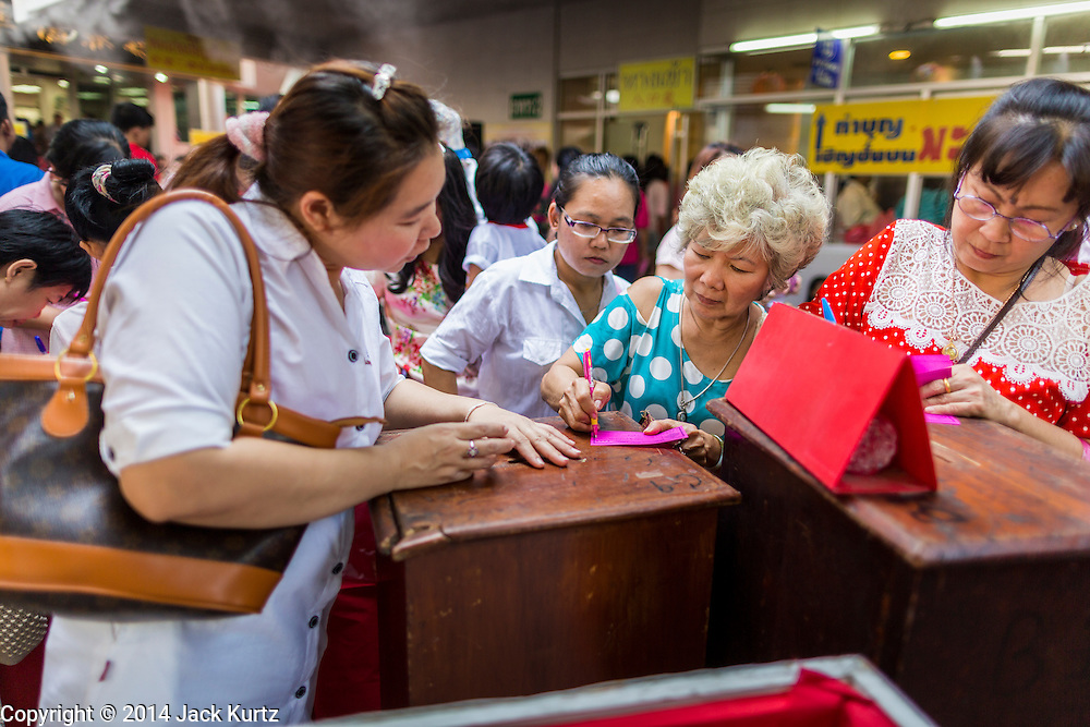 31 JANUARY 2014 - BANGKOK, THAILAND:   People make donations to buy coffins for the indigent at the Poh Teck Tung shrine during Lunar New Year festivities, also know as Tet and Chinese New Year, in Bangkok. This year is the Year of the Horse. Ethnic Chinese make up about 14% of Thailand and Chinese holidays are widely celebrated in Thailand.     PHOTO BY JACK KURTZ