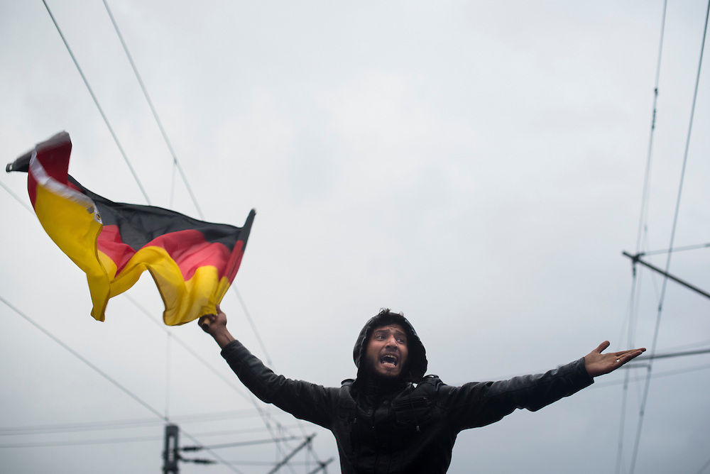 A refugee waves a German flag while leading chants imploring authorities to open the border at a refugee camp on the Macedonian (FYROM) border on March 7, 2016 in Idomeni, Greece.