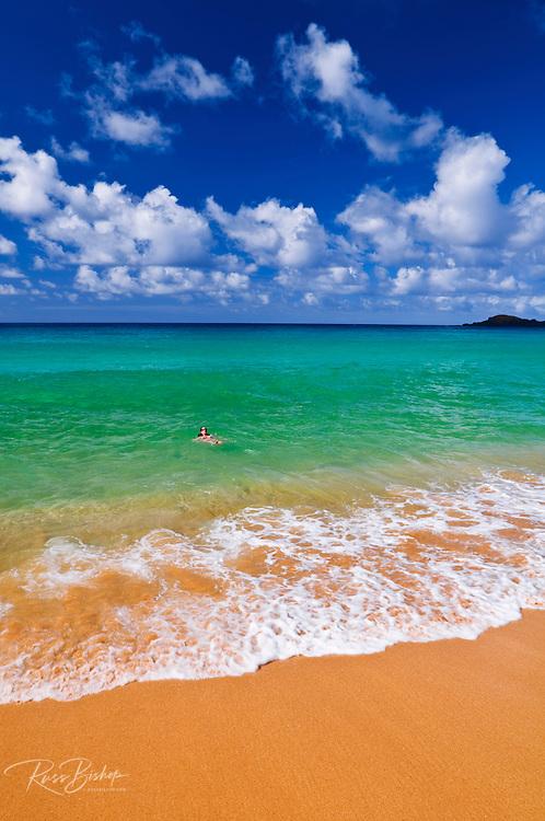 Woman enjoying the blue green waters at Secret Beach (Kauapea Beach), Island of Kauai, Hawaii USA