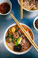 A bowl of Bun Bo Hue with beef, crab balls, blood sausage and herbs, a local specialty in Hue, Vietnam.