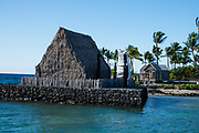 """A 1970s model of Ahu'ena Heiau stands in Kamakahonu National Historic Landmark, in Kailua-Kona, on the Big Island, Hawaii, USA. The site of Kamakahonu (""""eye of the turtle"""") is important as not only the last residence of Kamehameha I, who united all of the Hawaiian Islands, but also as the capital of the Kingdom of Hawaii, and where the Hawaiian system of kapu was ended (with the 1819 Ai Noa feast) and where the first Christian missionaries landed on the islands (in 1820). With Kamakahonu's original buildings gone, the Landmark is now part of King Kamehameha's Kona Beach Hotel, built in 1975. Ahu'ena Heiau, the Hawaiian religious temple that served Kamehameha the Great from 1812-1819, was rebuilt in the 1970s as the 2/3 scale model replica seen today (where no entry is allowed, out of respect). Hawaii's state flag (1959-present) had also previously been used by the 1810 kingdom, 1893 protectorate, 1894 republic, and 1898 territory of Hawaii. Protected by Kailua Pier in Kailua Bay, snorkeling from Kamakahonu Beach is good around Ahu'ena Heiau if you avoid boat routes."""