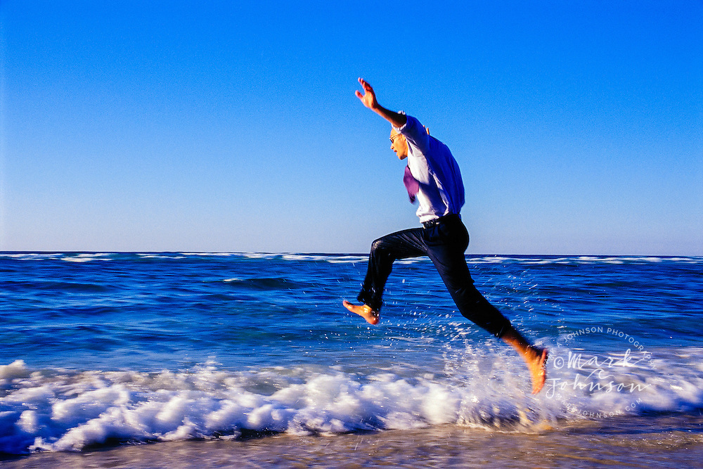 Australia --- Businessman Jumping near the waves on the beach ****Model Release available